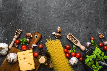 Italian food, cooking ingredients of spaghetti: pasta, tomatoes, basil, garlic, olive oil and cheese Фото со стока