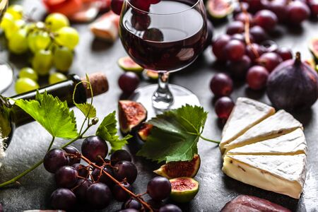 Buffet with wine and food. Fruit and cheese: wine appetizer on table.