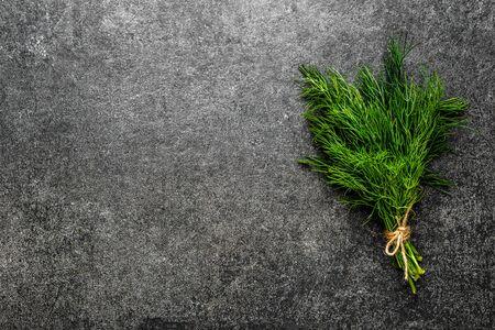 Green fresh dill herb on dark background.