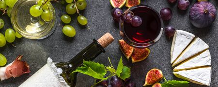Buffet with wine snack set or appetizer. Italian meat, glasses of wines, cheese, grapes and figs. Food background.