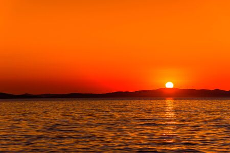 Background with landscape of sunset over sea with sun on the mountains horizon, Zadar, Dalmatia, Croatia