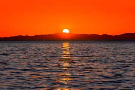 Beautiful red sunset over the sea with sun reflection in the water and mountains on the horizon, view from beach in Zadar, Dalmatia, Croatia Banco de Imagens