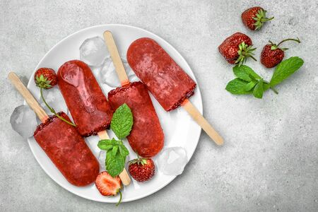 Fresh fruit popsicles with red strawberry, frozen sorbet. Juicy homemade ice cream with fruits, refreshing food concept.