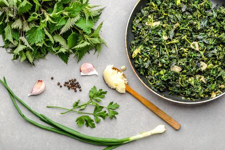 Cooking green vegetables. Healthy food, vegetarian pesto with green nettle and fresh stinging nettles leaves fried with garlic and spices on frying pan. Banco de Imagens