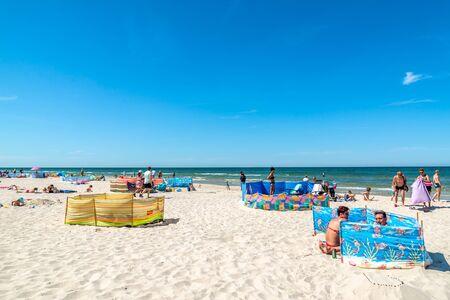 LEBA, POLAND - JUNE 09, 2019: Sunbathing people on the beach, sand, sea, summer vacation concept Sajtókép