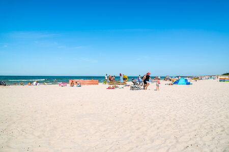 LEBA, POLAND - JUNE 09, 2019: People on the beach, summer vacation concept with sunbathing over sea and blue sky Sajtókép