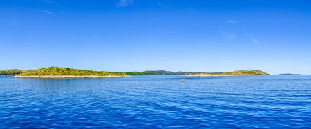 Croatian islands in the sea and blue sky. Croatia, panorama. Vacation and travel concept.