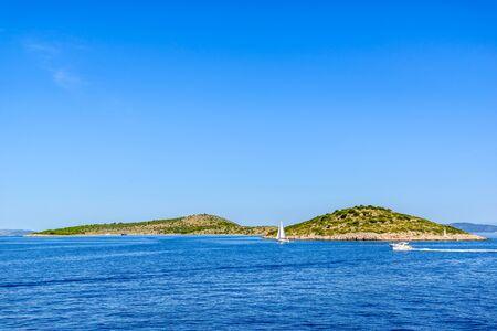 Adriatic coast with rocky beach, small islands, boats and sailing yachts in the blue sea, Croatia, Dalmatia