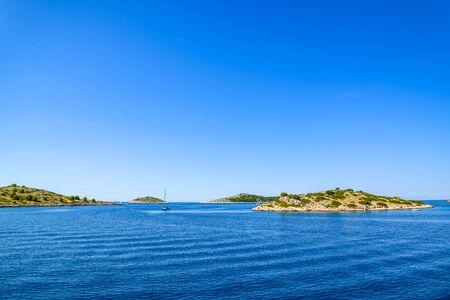 Adriatic coast with rocky beach, small islands, boats and sailing yachts in the blue sea, Croatia, Dalmatia Stock fotó - 145645543
