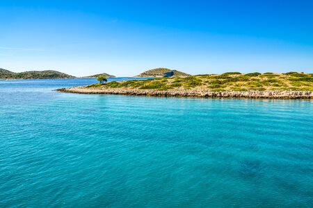 Beautiful lagoon with turquoise water of sea. Mediterranean scenery with blue sky, sea and island. Croatia, vacation travel concept.