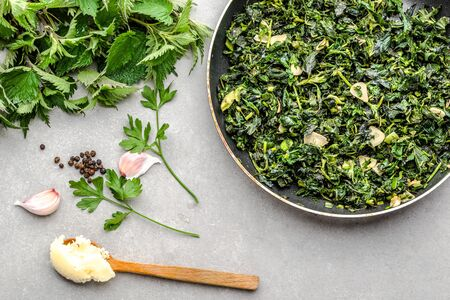 Cooking green food. Healthy, dieting, vegetarian pesto with green nettle and fresh stinging nettles, leaves fried with garlic and spices on frying pan. Stock fotó - 145465827