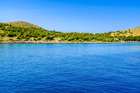 Adriatic coast of island with green pines and rocky beach, Mediterranean Sea, Croatia, Dalmatia Stock fotó - 145697490
