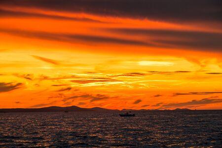 Beautiful orange sky with sunset over the sea, landscape from the beach in Zadar, Dalmatia, Croatia, Europe