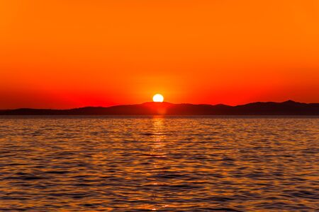 Beautiful orange sunset over the sea with sun on the mountains horizon, view from beach in Zadar, Dalmatia, Croatia, Europe Stock fotó - 145645597
