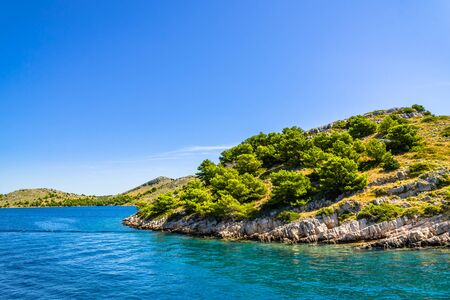 Croatian island with green pines and rocky coast. Mediterranean nature, blue sky and Sea in Croatia, vacation travel concept. Stock fotó - 145645600