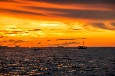 Background with landscape of sunset over sea under orange sky view from beach in Zadar, Dalmatia, Croatia