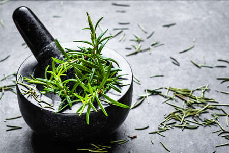 Fresh rosemary on black background. Mortar with herbs. Stock fotó