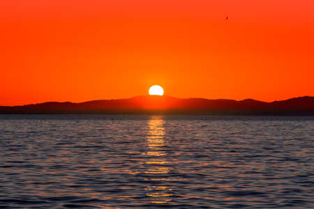 Beautiful orange sunset over the sea with sun reflection in the water and mountains on the horizon, view from beach in Zadar, Dalmatia, Croatia