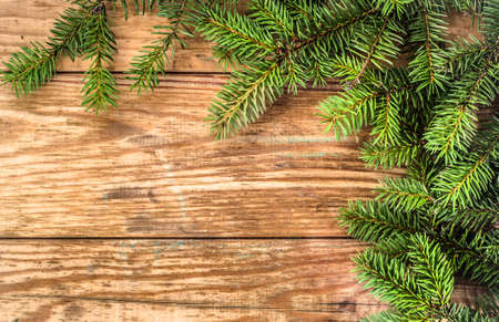 Christmas tree twigs of spruce arranged on aged wooden planks background useful as holiday background in vintage style.