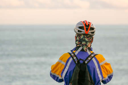 bicycle athlete looking out at sea view, sportswoman in colorful clothes and bike looking out to sea view with helmet Stock Photo