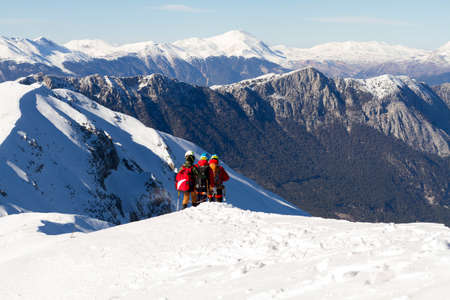 3 mountain climbers walk on snow in the mountains