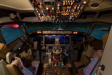 A view of the cockpit of a large commercial airplane a cockpit . Cockpit view of a commercial aircraft cruising Control panel in a plane cockpit.