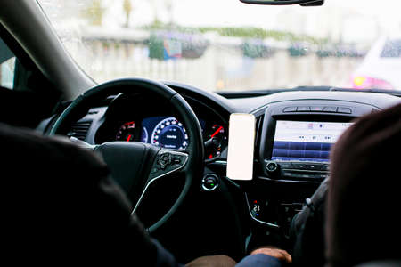 Inside view of the car and mobile phone by the steering wheel, copy space