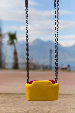 Empty swing with yellow and red colors in Antalya