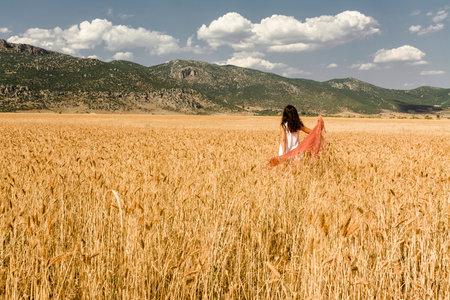 A woman in a scarf walking through a barley field in Antalya Turkey