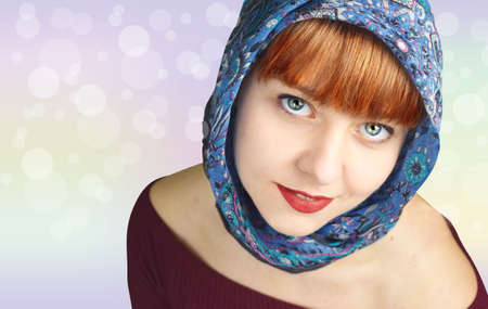 head scarf: red-haired girl, smiling with head scarf on light colored background