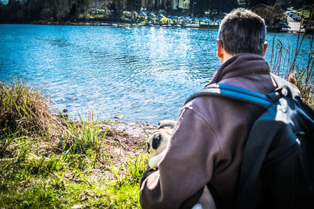 shot from behind: man sitting and shot from behind, watching the river