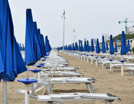 seafronts: Parasols and deck chairs on the Beach during a storm in rough seas, at lignano sabbiadoro Italy Stock Photo