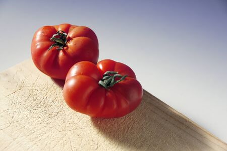 Fresh tomatoes on a wooden board.