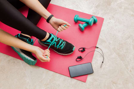 Stock photo of a young woman tying her shoelaces at home in the living room for fitness Standard-Bild