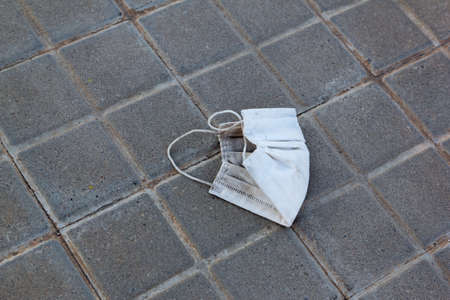 Stock photo of a used mask lying on the ground in the city. Masks become waste and garbage Stockfoto