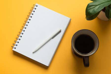 Stock photo of a blank open notebook page with pencil, coffee and a plant on a yellow background Banque d'images