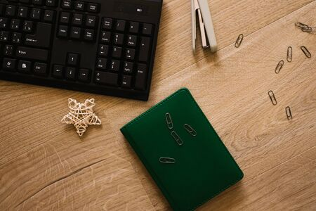 Keyboard, Stapler and paper clips with notebook on wooden table