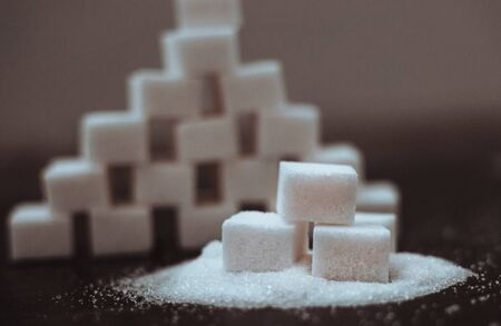 Sugar cubes stacked in a pyramid on a dark background. Harmful to health. Diabetes.