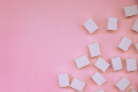 Lump sugar on a pink background. Sugar texture. White sugar. Diabetes.Harmful to health.Sugar cubes are scattered.