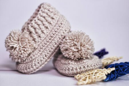 Small children's socks. Booties in gray on a white background. Wool socks for the baby. 版權商用圖片
