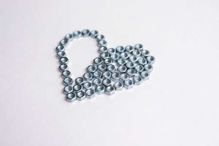 Heart laid out of bolts, nuts on a white background. Fathers Day and wedding anniversary concept.