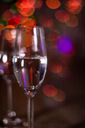 Champagne glasses on the background of Christmas lights. Christmas garland in the background. Degradation. 免版税图像