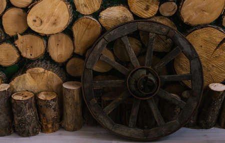 A wooden wheel stands near a wall of logs. The old wheel. Decor.