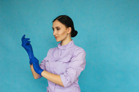 A young girl is wearing blue medical gloves on a blue background. A nurse or doctor is preparing for work. Personal protective equipment.