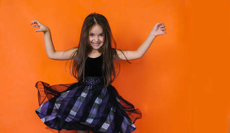 The girl jumps and the dress splits on the orange background. Fancy dress for Halloween. Children's holiday.