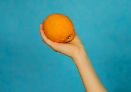 A woman's hand holds a ripe orange on a blue background. Citrus fruit. Healthy diet.