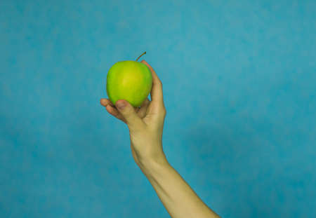 A woman's hand holds a ripe Apple on a blue background. Healthy diet.Vitamins.