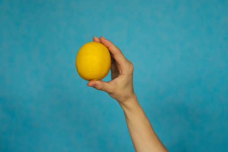 A woman's hand holds a ripe lemon on a blue background. Citrus fruit. Healthy diet. 免版税图像