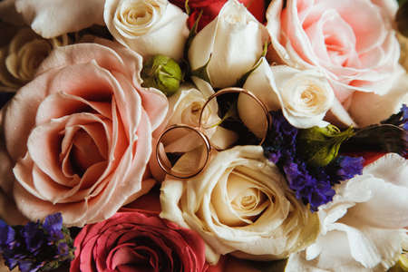 Wedding rings on the brides bouquet. Beautiful brides bouquet with roses.