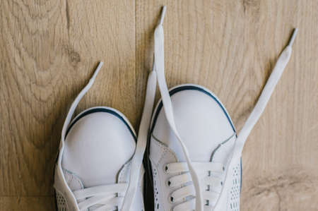 White sneakers with untied laces. Casual shoes. Shoes for sports.